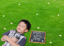 Sleeping boy with magnifying glass in grass field Stock Images
