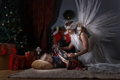 Sleeping boy near Christmas tree. Woman with angel wings and sleeping boy near Christmas tree.Conceptual Christmas image Stock Photos