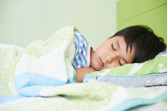 Sleeping boy. Preteen mixed-race boy sleeping in his bed Stock Images