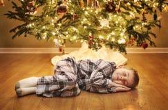 Sleeping boy waiting for Santa. A young boy sleeps under the Christmas tree while waiting for Santa Stock Photo