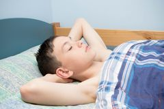 Sleeping boy. Young caucasian teenage boy asleep in his bed Royalty Free Stock Images