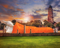 Sleeping buddha statue and ancient brick pagoda against beautifu Stock Photo