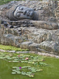 Sleeping buddha statue with lotus  flowers Stock Photos