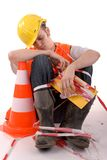 Sleeping builder with safety cone. Stock Images