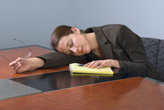Sleeping business woman. A tired business woman sleeping on a conference table Royalty Free Stock Images