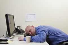 Sleeping Businessman. A exhausted and sleeping office worker with his head on the computer keyboard stock image