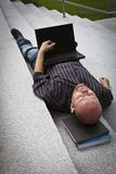 Sleeping Businessman. A sleeping / resting / exhausted man working with his computer / laptop in stairs outside Royalty Free Stock Photo