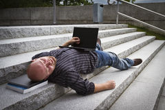 Sleeping Businessman. A sleeping / resting / exhausted man working with his computer / laptop in stairs outside Stock Photos