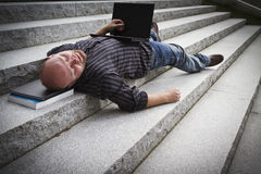 Sleeping Businessman. A sleeping / resting / exhausted man working with his computer / laptop in stairs outside Stock Image