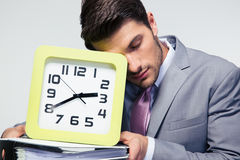 Sleeping businessman holding folders and clock Stock Photo
