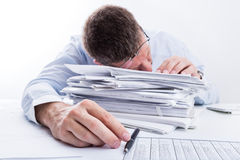 Sleeping Businessman. Tired businessman asleep at office desk full of papers. Shallow depth of field Royalty Free Stock Image