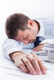 Sleeping Businessman. Tired businessman asleep at office desk full of papers. Shallow depth of field Royalty Free Stock Photo