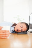 Sleeping businesswoman holding coffee in office Stock Photo