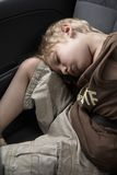 Sleeping in a car. Boy, sleeping in a car, with fastened safety belt Stock Image