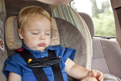 Sleeping Cargo. A one year old, blonde haired baby boy in a blue shirt, sitting in a buckled car seat in the back of a vehicle, sound asleep with his eyes closed Stock Photo