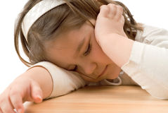 Sleeping Child. A young girl who fell asleep on a wooden desk Stock Images