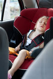 Sleeping child in auto baby seat stock image