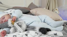 Sleeping child, baby sleeps on a bed among pillows and blankets, little boy asleep in his parents` house in the winter stock video footage