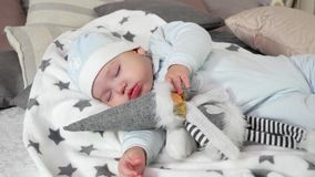 Sleeping child, baby sweetly sleep hugging toy, little boy asleep in his parents` house in the winter, cozy atmosphere stock video