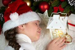 Sleeping child girl portrait with christmas decoration and candle lantern, dressed in santa hat, winter holiday concept Royalty Free Stock Photos