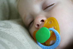 Sleeping Child with Pacifier. A child sleeps on a pillow with a pacifier in his mouth Stock Photography