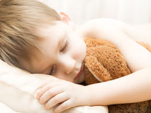Sleeping child with a teddy bear Stock Photo