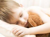 Sleeping child with a teddy bear Stock Photo