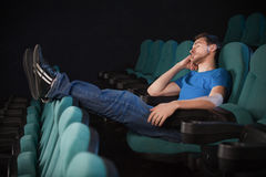 Sleeping at the cinema.. Side view of young man sleeping at the cinema and holding his hand on chin Royalty Free Stock Photo