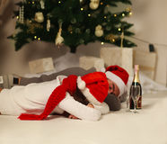 Sleeping couple in red hats under the Christmas tree Royalty Free Stock Photo
