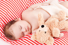 Sleeping cute little baby on red and white stripes pillow Stock Images