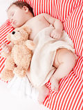 Sleeping cute little baby on red and white stripes pillow Royalty Free Stock Photography