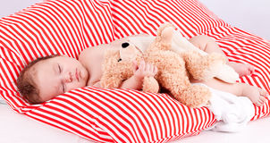 Sleeping cute little baby on red and white stripes pillow. With teddy bear royalty free stock images