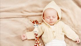 Little cute newborn baby boy sleeping with giraffe. Sleeping cute newborn baby, maternity concept, soft image of beautiful family stock photography