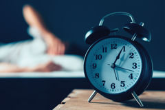 Sleeping disorder or insomnia. Concept, selective focus of vintage clock in bedroom and out of focus male person trying to fall asleep in bed Stock Photography