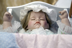 Sleeping Doll. In white crib with hands held up stock photo