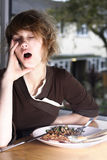 Sleeping during early breakfast. Woman to tired in the morning to eat her breakfast Stock Photo