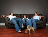 Sleeping family. A family sleeping on a couch with a chihuahua Royalty Free Stock Images