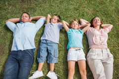 Sleeping family lying on the grass in a row. In the park on sunny day Stock Image