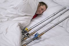 Sleeping fisherman in bed with fishing tackles. Think and dream about big fish trophy. Sleeping fisherman in bed with fishing tackles. Think and dream about big royalty free stock photos