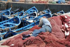 Sleeping in the Fishing nets. A young boy sleeping in the fishing nets at the harbor of the seaside village of Essaouira, Morocco stock images