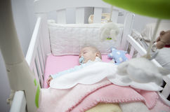 Sleeping four month baby boy lying in cot with mobile Stock Image