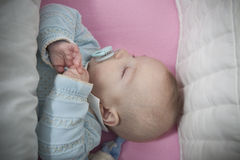 Sleeping four month baby boy lying in cot Royalty Free Stock Image