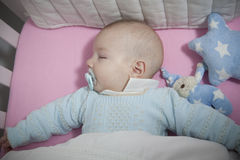 Sleeping four month baby boy lying in cot Royalty Free Stock Images