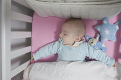 Sleeping four month baby boy lying in cot Stock Photo