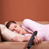 Sleeping in front of TV. A young woman sleeping on a sofa in front of a TV with the remote control slipping out of her hand. Lots of copyspace Royalty Free Stock Photo