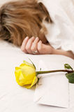 Sleeping girl. Girl is sleeping on a big bed with white bedclothes and yellow rose on a pillow Stock Images