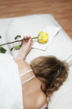 Sleeping girl. Girl is sleeping on a big bed with white bedclothes and yellow rose on a pillow Royalty Free Stock Image