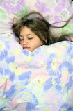 Sleeping girl. Little angel is smiling in her sleep, enjoying comfortable bed with colorful softy linen Stock Photos