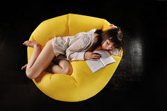 Sleeping Girl. With a book on a yellow chair Stock Photos