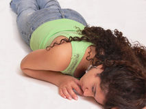 The sleeping girl. An sleeping girl, laying in jeans on the floor on her stomach and her Stock Photo